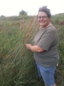 Windswept Rhonda trying to hold still some Big Bluestem to see how tall it is. Tallgrass Prairie National Preserve.